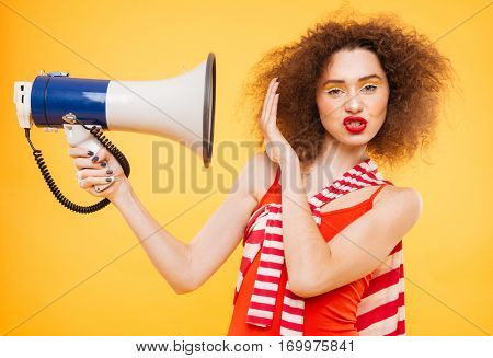 Displeased Bright model with megaphone. Woman covering by the megaphone. Isolated orange background