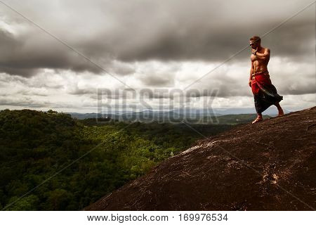 Athletic guy standing on a rock on a background of a stormy sky. Sri Lanka. Mulkirigala Raja Maha Viharaya. View from above.