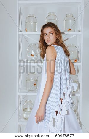 Charming young woman standing near the closet with gold fishes in jars on the shelves
