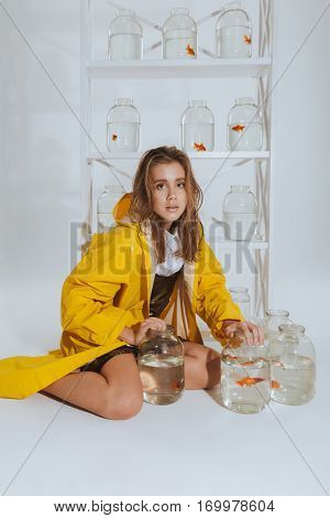 Beautiful young woman in yellow raincoat sitting and holding jars with gold fishes