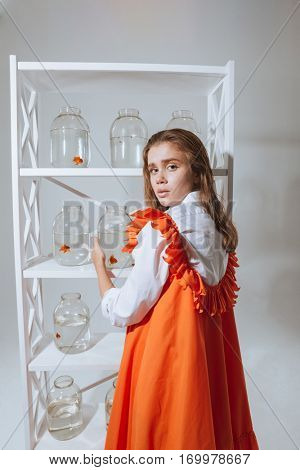 Beautiful young woman standing and taking jar with gold fish from the closet