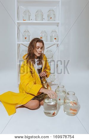 Lovely young woman in yellow raincoat sitting on the floor near jars with gold fishes