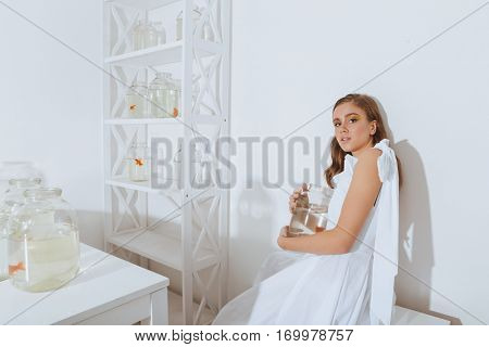 Relaxed young woman with gold fish in jar sitting and leaning on the wall in the room