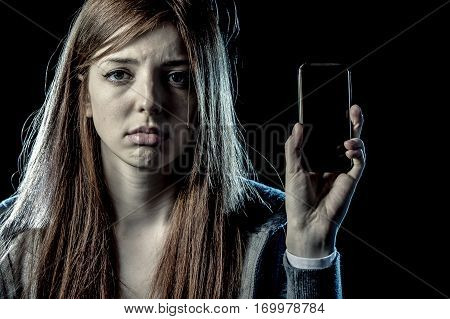 teenager girl or young woman holding mobile phone as internet stalked victim abused in cyberbullying or cyber bullying stress concept and in smartphone and network addiction concept