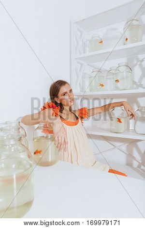 Beautiful young woman sitting at the table with gold fishes in jars over white background