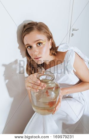 Portrait of charming young woman in white dress with gold fish in jar