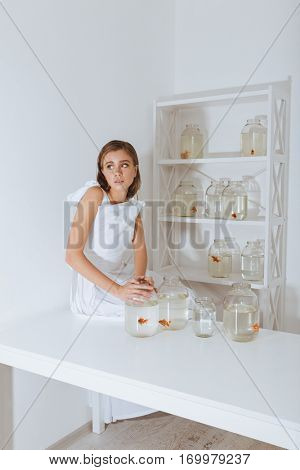 Cute young woman sitting on the table and holding jar with gold fish in the room