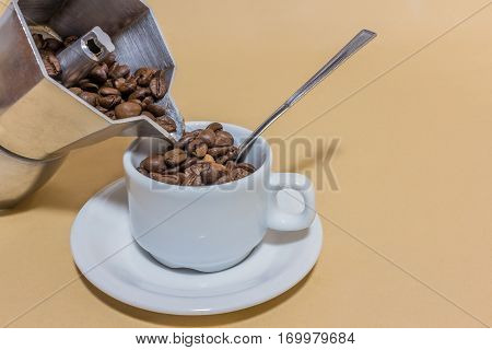 A coffeepot with the coffe beans ina cup of coffee