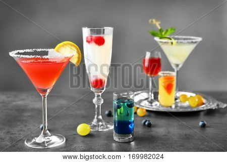Different cocktails with sweet berries on gray table