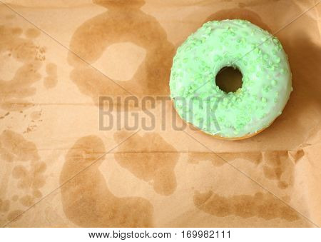 Delicious donut on greasy paper in box