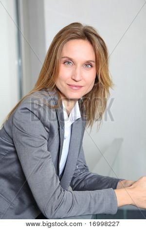 Portrait of blond businesswoman in grey jacket