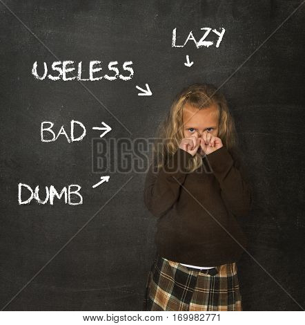 little beautiful blond schoolgirl sad ashamed and embarrassed being pointed and marked on school class blackboard with the words lazy useless bad and dumb in abuse discipline concept