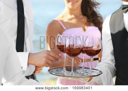 Waiter serving wine at party outdoors, close up view
