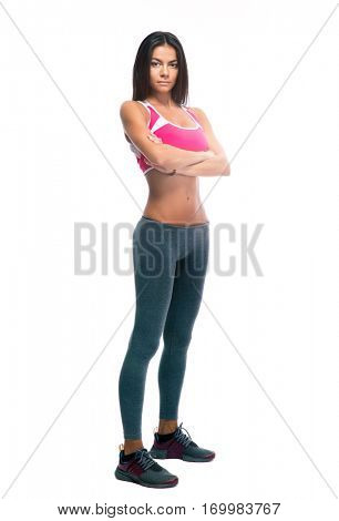 Full length portrait of a sporty woman standing with arms folded isolated on a white background. Looking at camera
