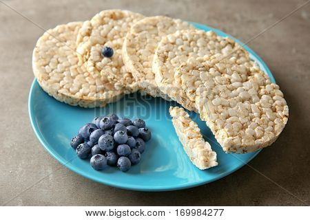 Plate with round rice crispbreads and blueberries on table