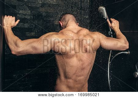 Muscular Fitness Bodybuilder Taking A Shower After Training. Close Up Details Of Back Muscles In Sho
