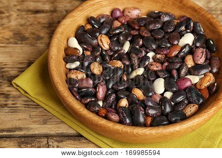 Bowl with dried haricot beans and napkin on wooden table