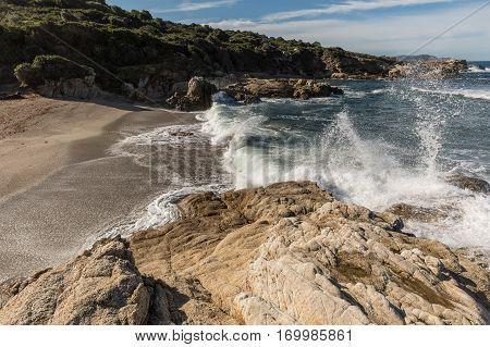 Waves Crash Onto A Small Sandy Cove Near Calvi In Corsica