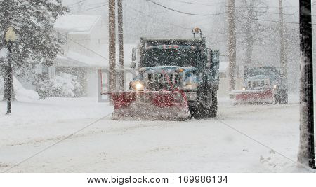 Two snow plows doing their job in the middle of a blizzard on a local street