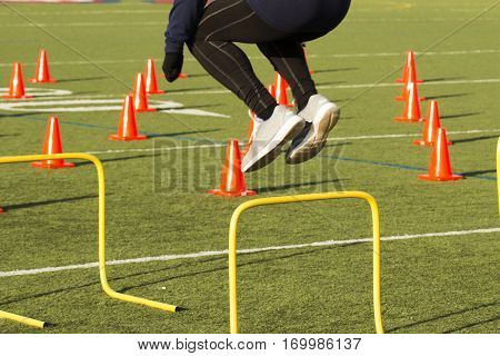 An athlete works out jumping over yellow hurdles on a green turf field with orange cones on it