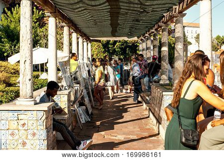 Lisbon, Portugal - Septmember 19, 2016: Viewpoint of Santa Luzia busy with tourists enjoying the beautiful scenery and painters selling their work