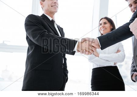 Business people shaking hands near the window in office with business woman on background. From below view