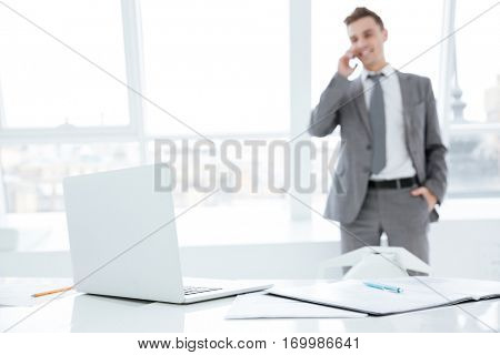 Smiling Business man talking at phone and standing near the window. Photo from the table with laptop. Focus on laptop. man on background