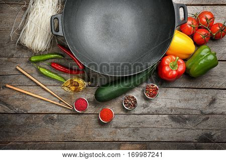 Wok with products on wooden background