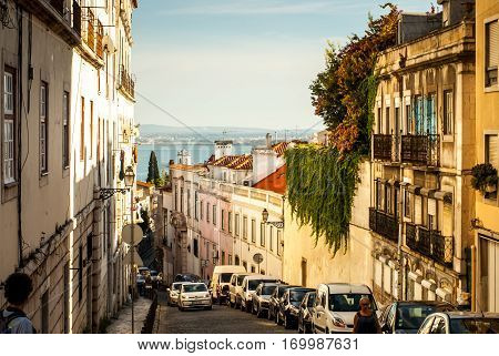 Lisbon, Portugal - Septmember 19, 2016: Street going up to the viewpoint of neighbourhood Graca busy with tourists enjoying the beautiful scenery