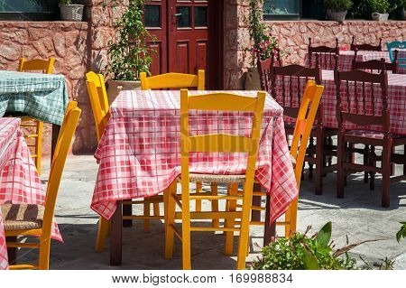 Orange wooden tables at traditional Greek tavern on Santorini island, Greece
