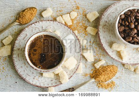 Coffee in a small cup with cane brown sugar and lump sugar on gray wooden background