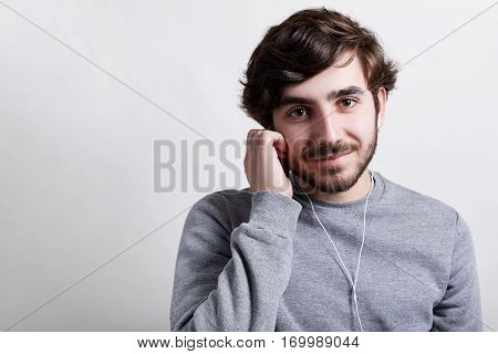 Young hipster with big dark eyes modern hairstyle and beard wearing casual grey sweater listening to the music or audiobook with his earphones holding his hand on earphones having happy expression