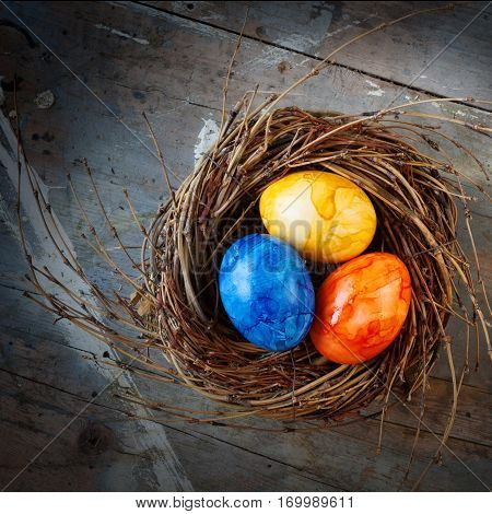 Colorful easter eggs in a nest from straw on a old shabby wooden table