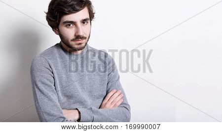 Headshot of fashionable young hipster with trendy hairstyle and thick beard dressed in grey sweater keeping his arms crossed having tires and thoughtful expression. Confident man with crossed hands