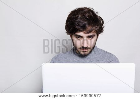 People emotions technology education. A serious stylish guy with trendy beard working with his laptop. A hipster student looking serious and concentrated working at his diploma paper