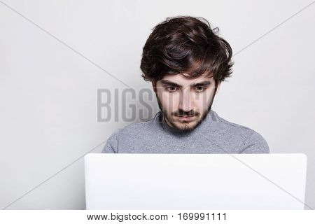 A handsome boy with stylish hairstyle and trendy beard looking with astonishment into the screen of his laptop computer reading some horrify news in the Internet. People and technology concept