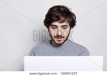 Attractive bearded man with sylish hairstyle wearing grey sweater spending free time using his laptop. Concept of young people enjoing mobile devices. Serious expression. White background