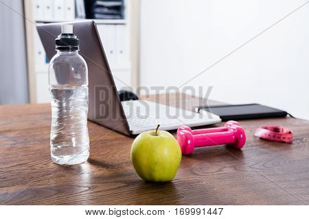 Close-up Of A Fitness Object Near Laptop On Wooden Desk