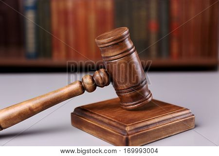 Judge's gavel with sound block and books on background
