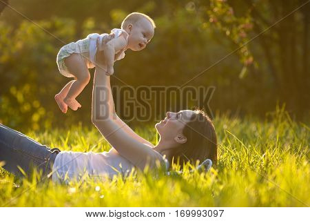 Cute cheerful baby on mother's hands lying on grass