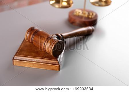 Gavel with sound block and scales on table