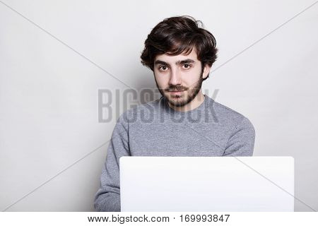 Handsome bearded man with sylish dark hair wearing casual grey sweater checking e-mail on laptop using free wireless internet connection looking directly into the camera with serious expression