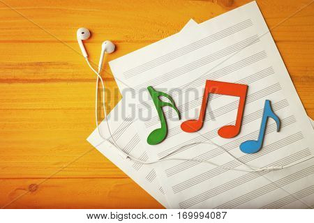 Colourful musical notes and earphones lying on music sheet on yellow wooden background