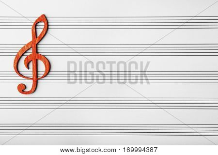 Wooden musical clef on music sheet background