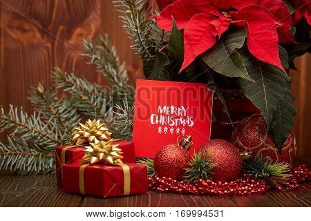 Christmas decoration with Red Poinsettia flowers (Euphorbia Pulcherrima), fir branch, gift boxes, red balls and beads on wooden background.  New year and Christmas background with copy space.