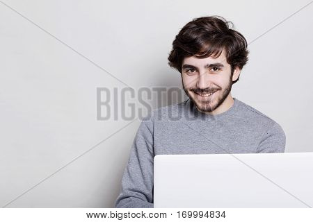 Emotions and feelings. A photo of positive man with cheerful expression having stylish beard and hairstyle dressed in casual clothes sitting in front of his laptop and smiling being pleased