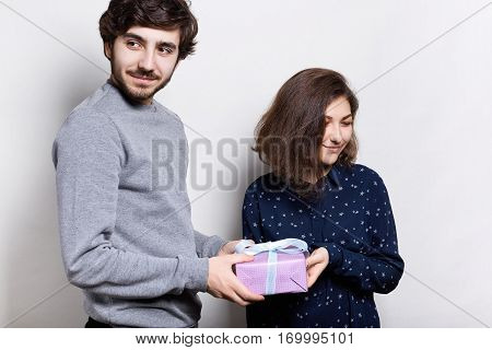 Younf beautiful couple with present isolated on white. A hipster bearded guy giving his girlfriend a present for a holiday. Happy woman receiving present from her lover.