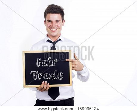 Fair Trade - Young Smiling Businessman Holding Chalkboard With Text
