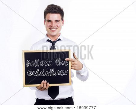 Follow The Guidelines - Young Smiling Businessman Holding Chalkboard With Text