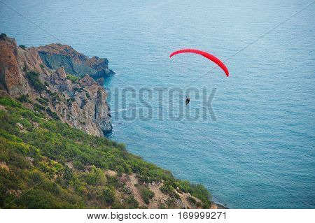 Paraglide silhouette flying above the sea against sunset sky